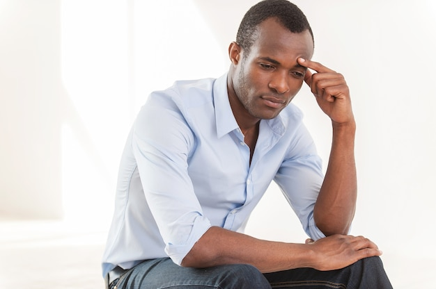 Thinking about... thoughtful young african man in blue shirt touching forehead with hand and looking away