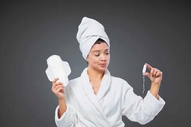 패드나 탐폰을 사용할 생각입니다. 우유부단한 여성이 목욕 가운을 입고 머리에 수건을 두르고 월경 기간 동안 위생 용품을 보관합니다. 여성용품, 화장품
