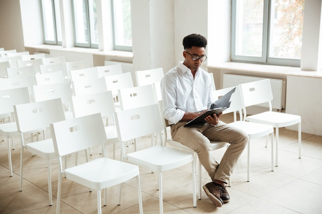 Thinking african man sitting coworking with clipboard