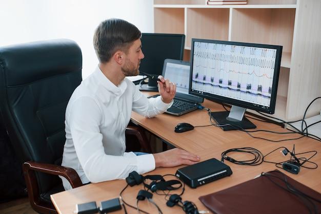 생각하고 결론 내리기. 거짓말 탐지기 검사관은 거짓말 탐지기 장비를 가지고 사무실에서 일합니다.