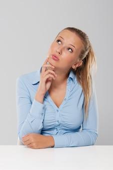 白い机に座っている思考と物思いにふける女性