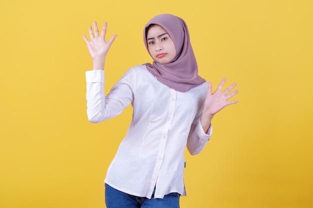 Думающая привлекательная девушка показывает что-то под рукой в хиджабе