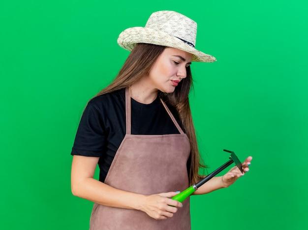Думая красивая девушка-садовник в униформе в садовой шляпе, держа и глядя на грабли мотыги, изолированные на зеленом фоне