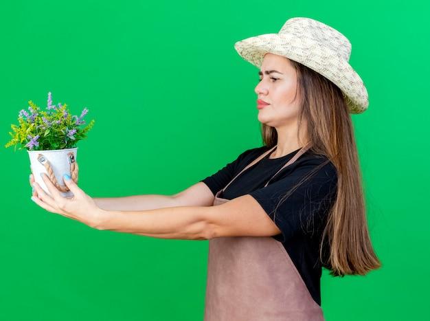 Pensando bella ragazza giardiniere in uniforme che indossa cappello da giardinaggio tenendo fuori fiore in vaso di fiori a lato isolato su sfondo verde
