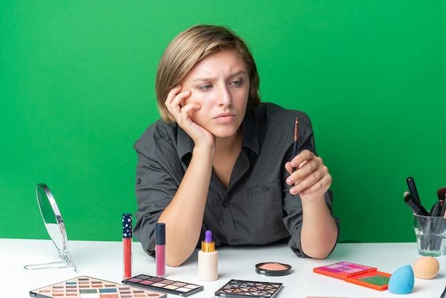 생각하는 아름다운 여성은 화장 도구를 들고 화장 브러시를 보고 테이블에 앉아 있다