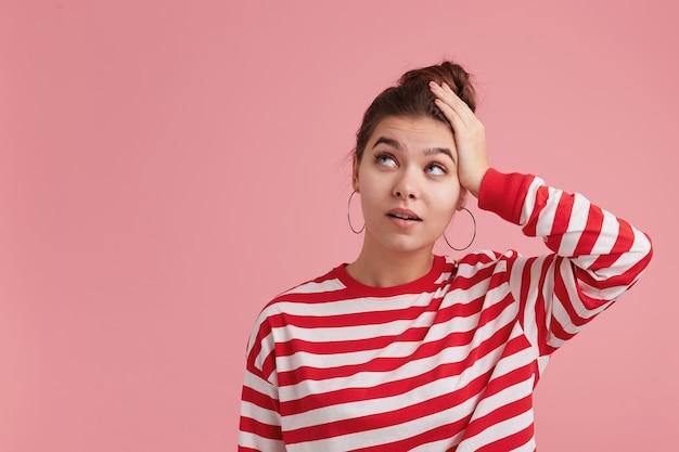 ピンクの壁に孤立して立っている、片手で頭を抱え、コピースペースで左隅を見上げている美しい若い女性を考えて