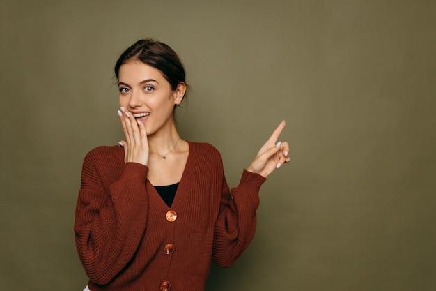 Мышление красивая молодая женщина, глядя в сторону на зеленом copyspace. обалденный кавказец, улыбчивый и радостный. фото высокого качества