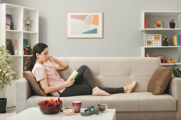 Il pensiero morde le unghie giovane ragazza sdraiata sul divano dietro il tavolino da caffè che legge un libro in soggiorno