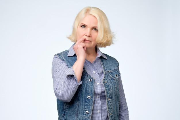 口の近くに手を握ってカメラを見て思考の金髪の年配の女性
