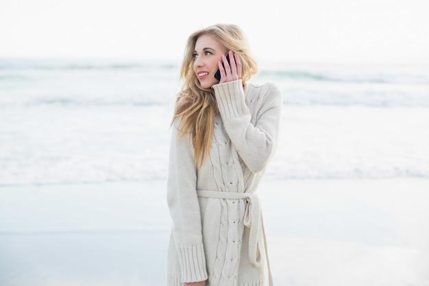Мышление блондинка в шерстяном кардигане, делая телефонный звонок