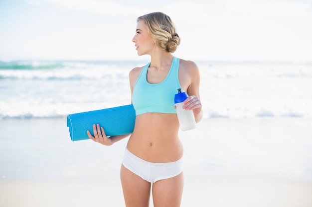 Thinking blonde woman in sportswear holding a bottle and an exercise mat