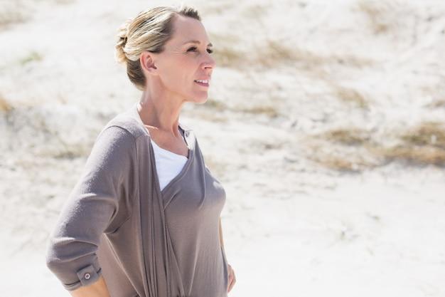 Мышление блондинка женщина, стоящая на пляже