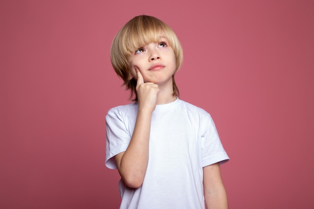 Thinking boy cute adorable blonde in white t-shirt on pink wall