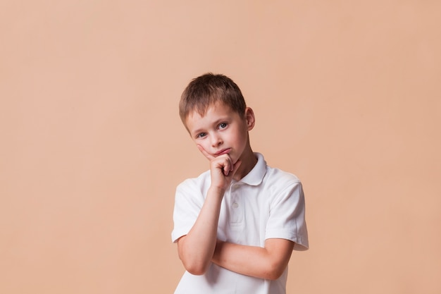 Thinking boy looking at camera standing in front of beige backdrop