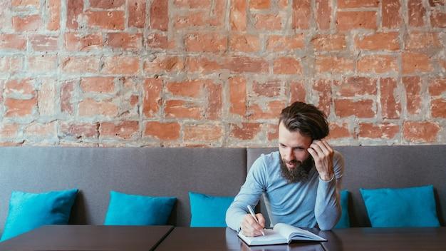 思考の頭脳と創造的なアイデアの生成。プランナーで書いている男。
