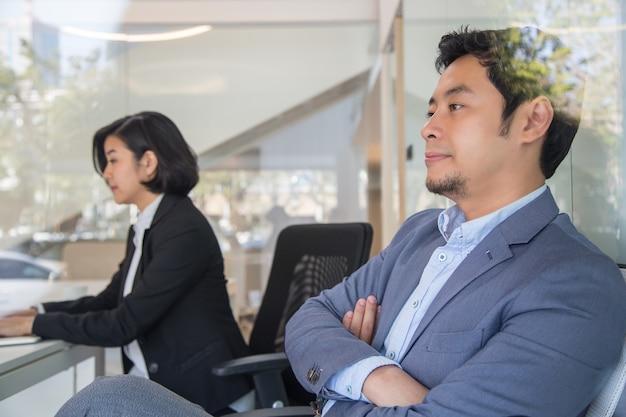 オフィスでの会議中にビジネスを考えています。楽しみにしているタイのビジネスマン、二人。
