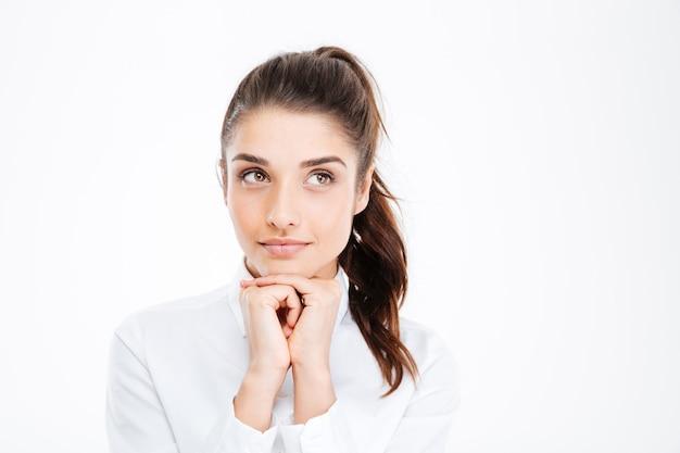 Думающая деловая женщина улыбается и смотрит на копию пространства над белой стеной