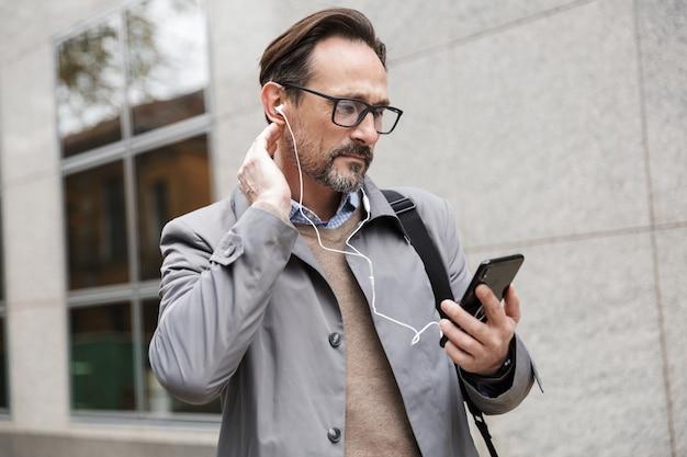 Думающий бизнесмен в очках с помощью мобильного телефона и наушников, стоя возле офисного здания