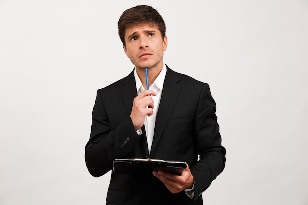 Thinking businessman standing isolated holding clipboard.