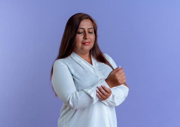 La donna di mezza età caucasica casuale di pensiero ha afferrato il polso isolato sulla parete blu