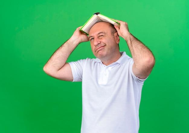 緑の壁に隔離された本で頭を覆ったカジュアルな成熟した男を考える