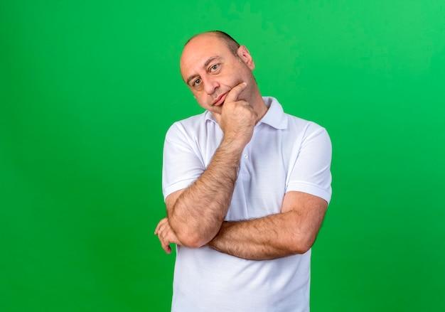 L'uomo maturo casuale di pensiero ha afferrato il mento isolato sulla parete verde