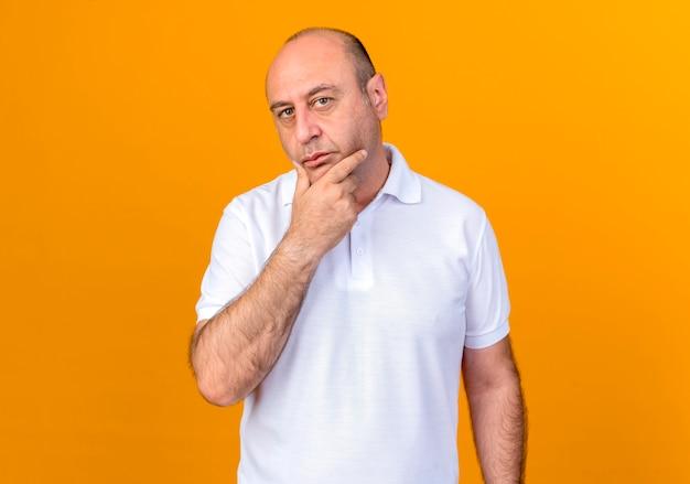 考えるカジュアルな成熟した男は黄色の壁に分離されたあごをつかんだ