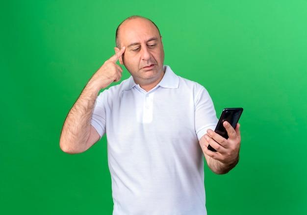 캐주얼 성숙한 남자를 생각하고 녹색 벽에 고립 된 사원에 손가락을 넣어 전화를보고