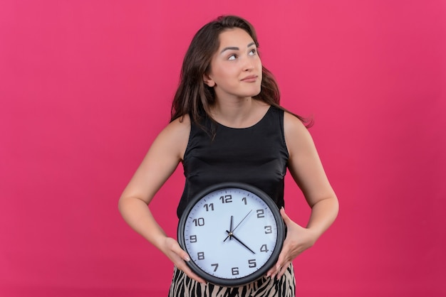 Thinking caucasian girl wearing black undershirt holding a wall clock on pink background
