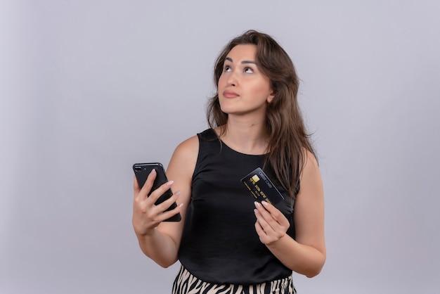 白い背景に電話とクレジットカードを保持している黒のアンダーシャツを着て考えている白人の若い女の子