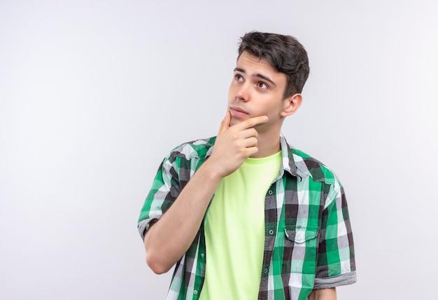 Il giovane tirante caucasico di pensiero che porta la camicia verde ha messo la sua mano sul mento su bianco isolato