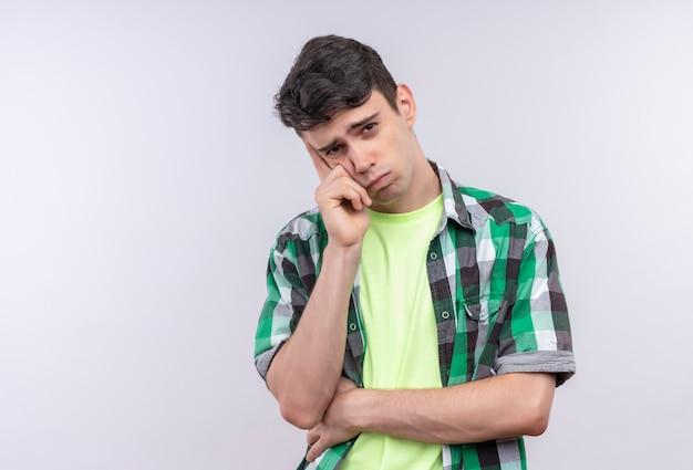 Думающий кавказский молодой парень в зеленой рубашке положил руку на щеку на изолированном белом
