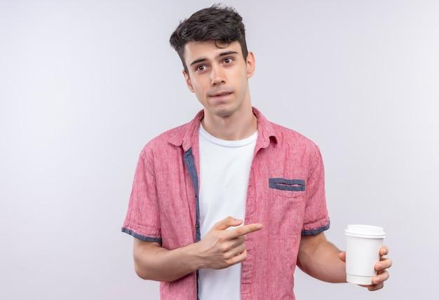 ピンクのシャツを着ている白人の若い男は、孤立した白のコーヒーを指しています
