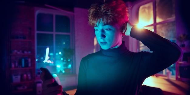 생각. 네온 조명 인테리어에 세련된 빨간 머리 남자의 영화 초상화. 보라색 - 파란색의 영화 효과처럼 톤. 실내에서 화려한 조명으로 스마트폰을 사용하는 백인 모델입니다. 전단.