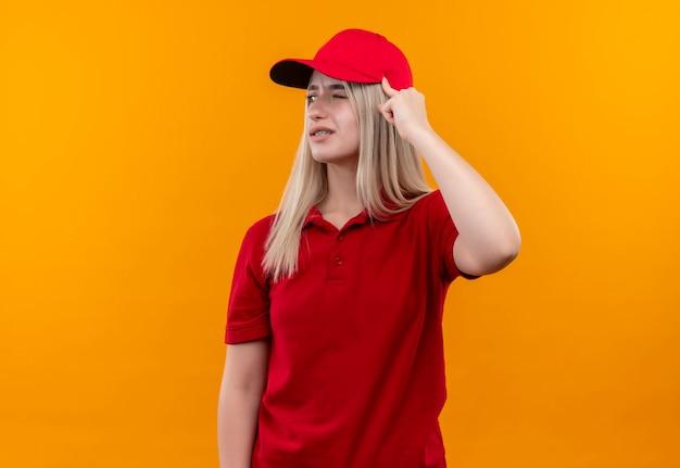 La ragazza giovane di consegna di pensiero che indossa la maglietta rossa e il berretto in parentesi graffa ha messo il dito sulla testa sulla parete arancione isolata