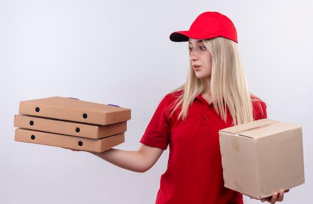 Ragazza giovane di consegna di pensiero che indossa la maglietta rossa e la scatola della tenuta del cappuccio che esamina la scatola della pizza sulla sua mano sulla parete bianca isolata