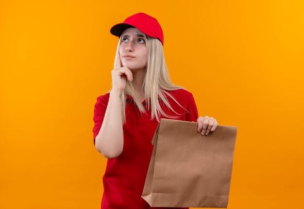 Pensando la ragazza di consegna che indossa la maglietta rossa e la scatola di carta della tenuta del cappuccio mise il dito sulla guancia sulla parete arancione isolata