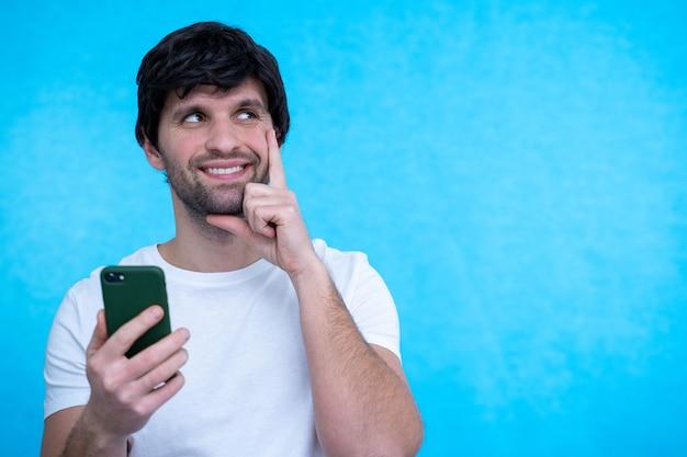 Думающий, мечтающий человек с помощью мобильного телефона позирует на синей поверхности стены