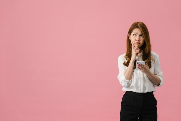 행복을 느끼는 캐주얼 의류를 입고 분홍색 배경에 고립 된 서 긍정적 인 표현으로 전화를 사용하여 꿈꾸는 젊은 아시아 아가씨를 생각합니다.