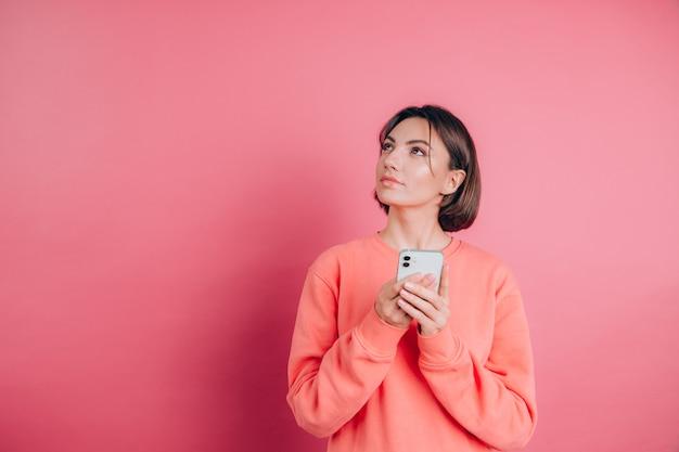 Думая, мечтающая молодая красивая женщина позирует изолированно на розовом фоне стены с помощью мобильного телефона