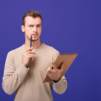 Thinking employee with notebook in left hand holds pen near face in right hand