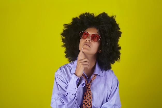 メガネと男性のシャツとネクタイで黄色の壁にアフロの巻き毛のヘアスタイルで考える女の子