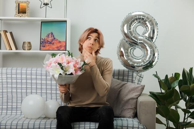 Il pensiero ha afferrato il mento bel ragazzo durante la felice giornata delle donne con in mano un bouquet seduto sul divano in soggiorno