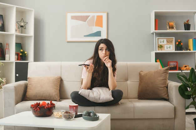 Thinking grabbed chin young girl holding phone sitting on sofa behind coffee table in living room