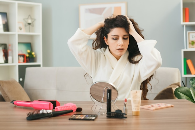 Thinking grabbed hair looking at mirror young girl sitting at table with makeup tools in living room