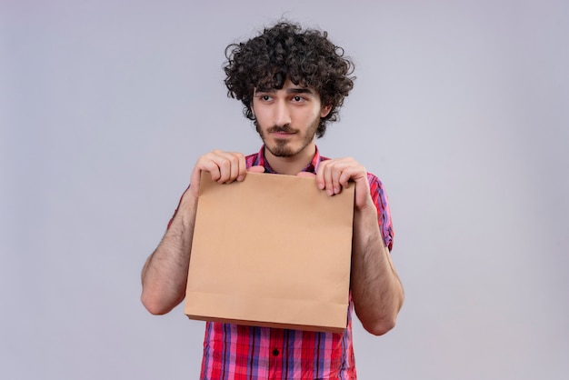 A thinking handsome man with curly hair in checked shirt holding shopping bag looking at the side