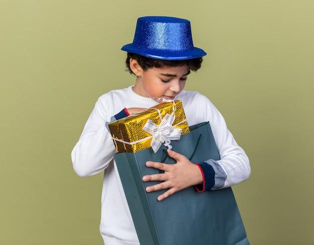 Думающий маленький мальчик в синей партийной шляпе держит и смотрит на подарочный пакет