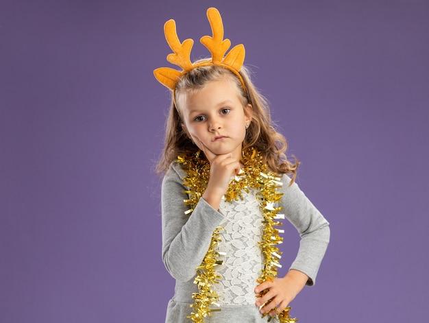 Pensando bambina indossa il cerchio dei capelli di natale con la ghirlanda sul collo mettendo il dito sulla guancia mettendo la mano sul fianco isolato su sfondo blu