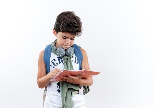 Думающий маленький школьник в сумке и наушниках пишет что-то на ноутбуке, изолированном на белом