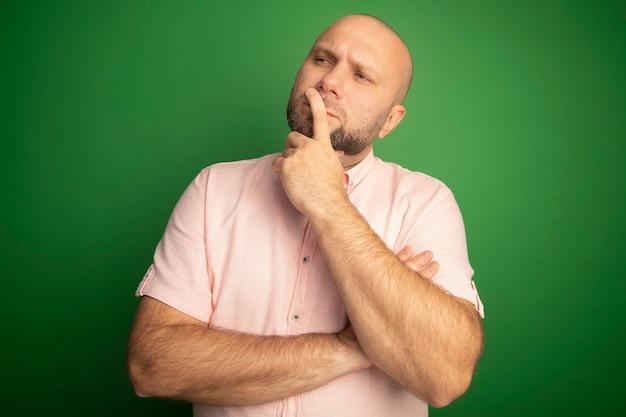 입에 손가락을 넣어 분홍색 티셔츠를 입고 측면 중년 대머리 남자를보고 생각